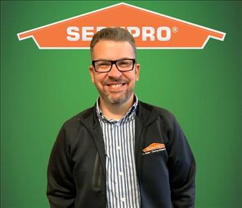 New employee standing in front of a SERVPRO backgound