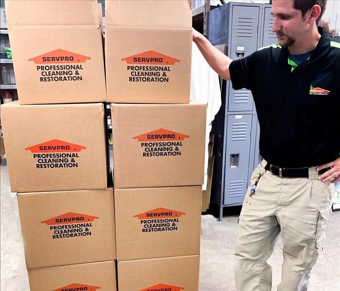 SERVPRO guy standing by a stack of SERVPRO boxes