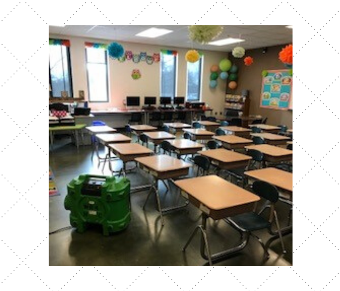 Classroom with desks lines up and a dehumidifier on the ground